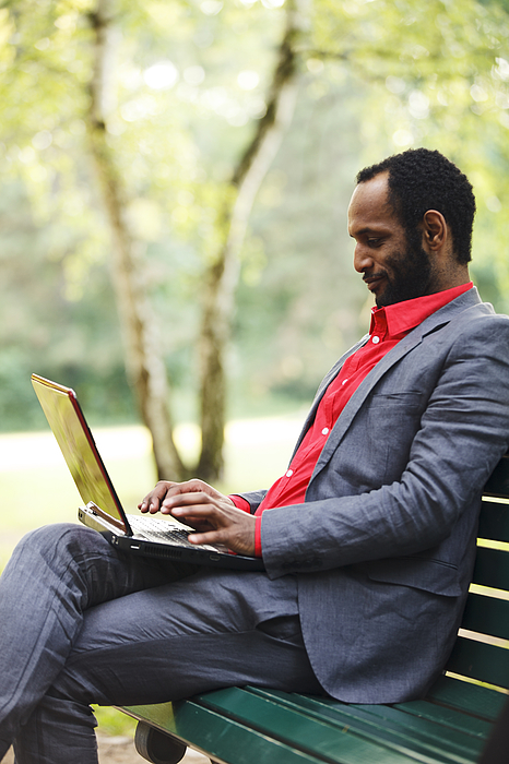 Businessman Working With Laptop In Park Photograph by Efenzi