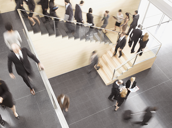 Businesspeople Walking In Busy Office Building Photograph by Robert Daly