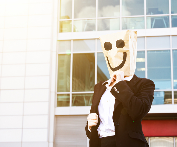 Businesswoman in smiling paper bag mask outside office building Photograph by RapidEye