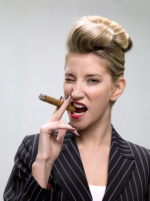 Businesswoman smoking cigar Photograph by Peter Dazeley