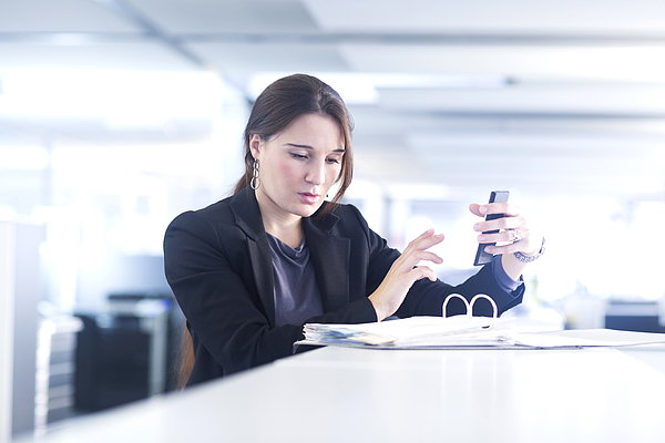 Businesswoman using smartphone in office Photograph by Sigrid Gombert