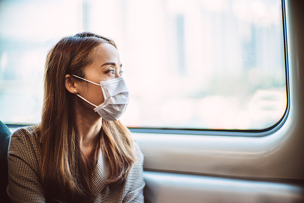 Businesswoman with protective face mask looking out of the window of train in thought Photograph by Images By Tang Ming Tung