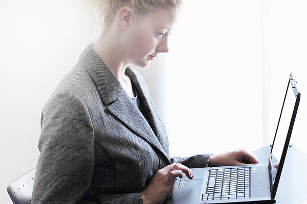 Businesswoman working on laptop Photograph by Sigrid Gombert
