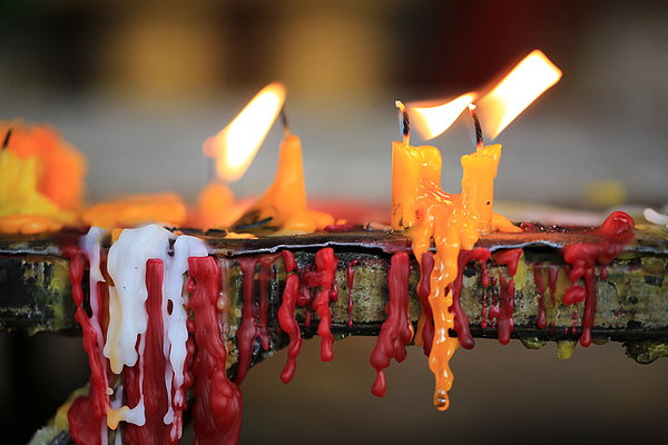 Candles in Wat Si Muang in Vientiane Laos. Photograph by Pinnee