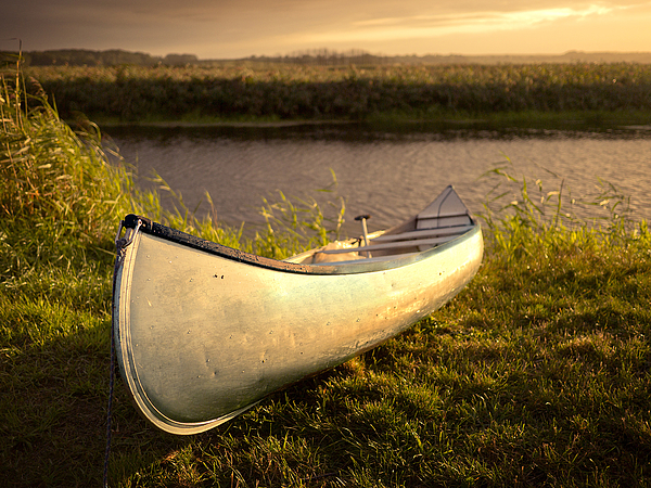 Canoe in evening light at the river bank Photograph by Bernd Schunack