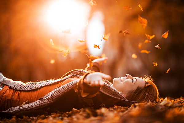 Carefree woman relaxing and throwing autumn leaves in nature. Photograph by BraunS