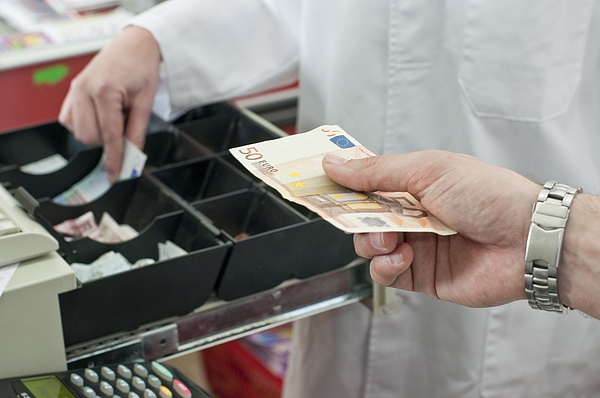 Cash In Hand Of Customer Paying In Supermarket Photograph by Chris Sattlberger