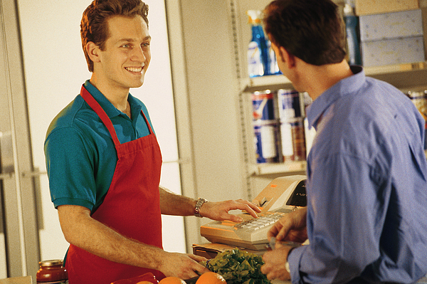 Cashier with customer at grocery store Photograph by Comstock