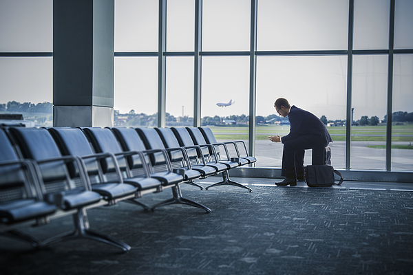Caucasian businessman sitting suitcase in airport Photograph by John Fedele