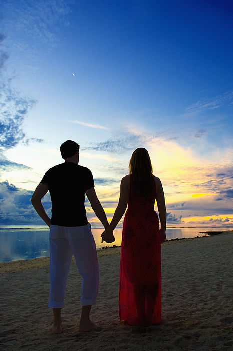Caucasian couple holding hands on beach at sunset Photograph by Jacobs Stock Photography Ltd