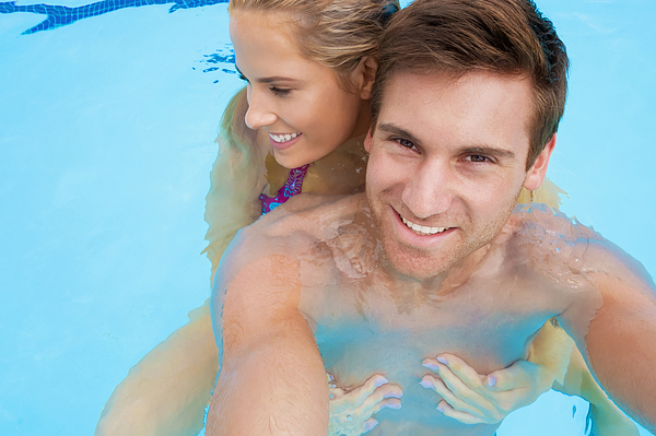 Caucasian couple together in swimming pool Photograph by Jacobs Stock Photography Ltd