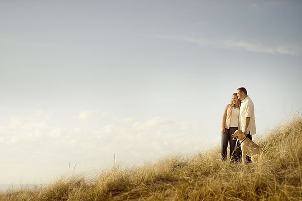 Caucasian couple walking dog on grassy dunes Photograph by Chris Clor