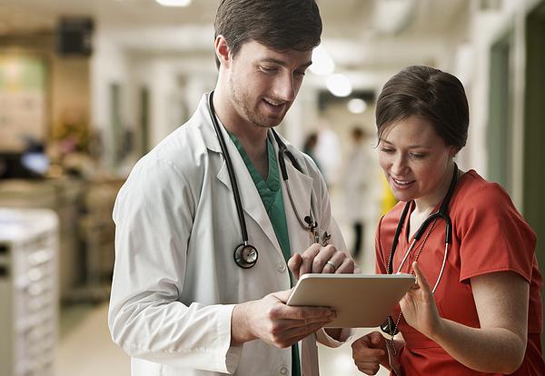 Caucasian doctor and nurse using tablet computer Photograph by Jose Luis Pelaez Inc