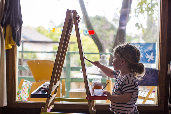 Caucasian girl painting on easel near window Photograph by Adam Hester