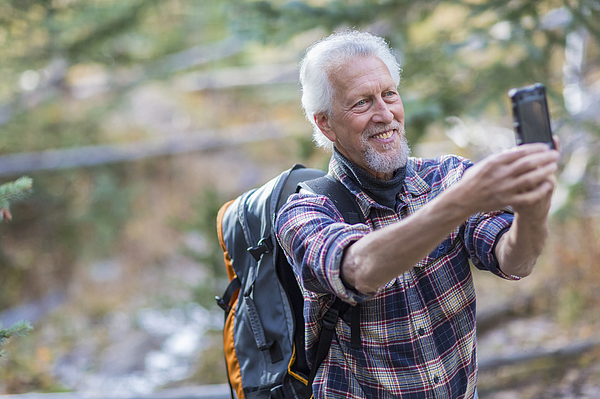 Caucasian hiker taking cell phone photograph in forest Photograph by Marc Romanelli