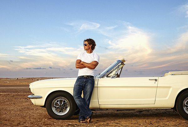 Caucasian man relaxing on convertible on remote road Photograph by Colin Anderson Productions pty ltd
