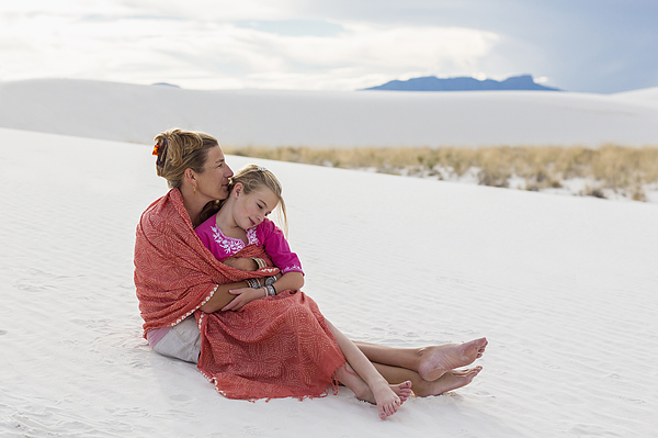 Caucasian mother and daughter wrapped in blanket on sand dune Photograph by Marc Romanelli