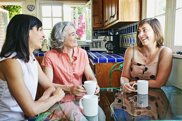 Caucasian mother and daughters drinking coffee in kitchen Photograph by Peathegee Inc