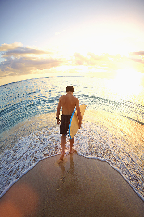 Caucasian teenage boy carrying surfboard on beach Photograph by Colin Anderson Productions pty ltd