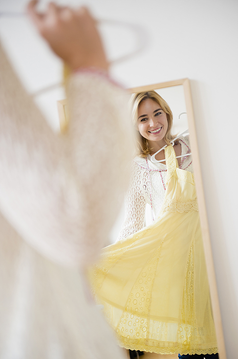 Caucasian woman admiring dress in mirror Photograph by JGI/Jamie Grill