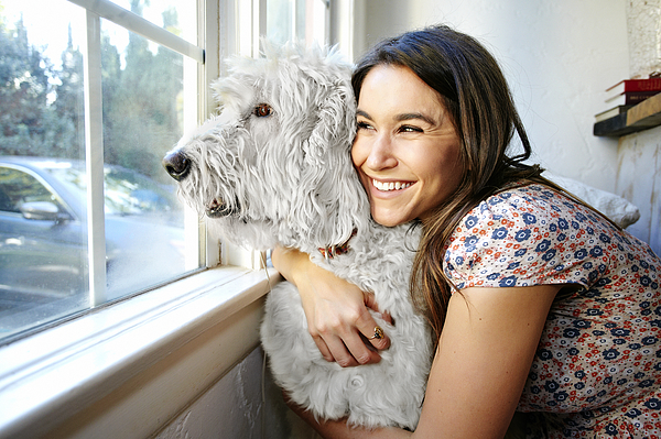 Caucasian woman hugging dog at window Photograph by Blend Images - Peathegee Inc