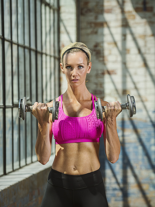 Caucasian woman lifting weights in warehouse Photograph by Erik Isakson