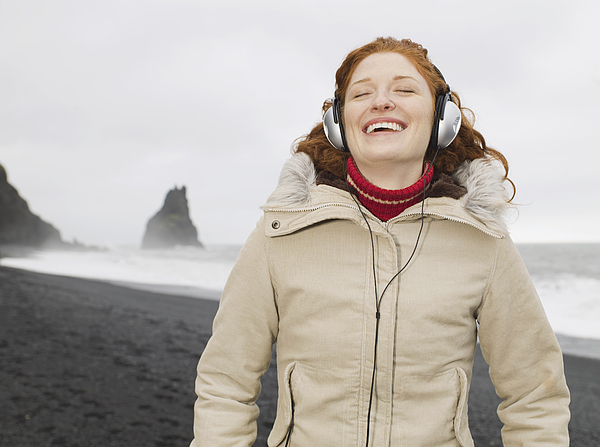 Caucasian woman listening to headphones on beach Photograph by Jacobs Stock Photography Ltd