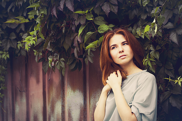 Caucasian woman standing under leaves by fence Photograph by Maxim Chuvashov