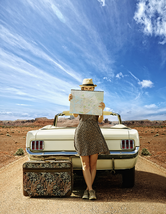 Caucasian woman with convertible reading map on remote road Photograph by Colin Anderson Productions pty ltd