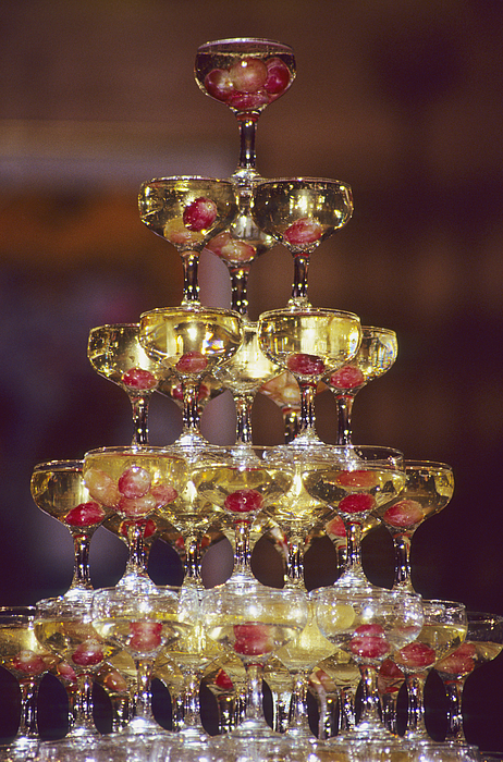 Champagne glass pyramid, glasses containing champagne and grapes Photograph by Stuart Gregory