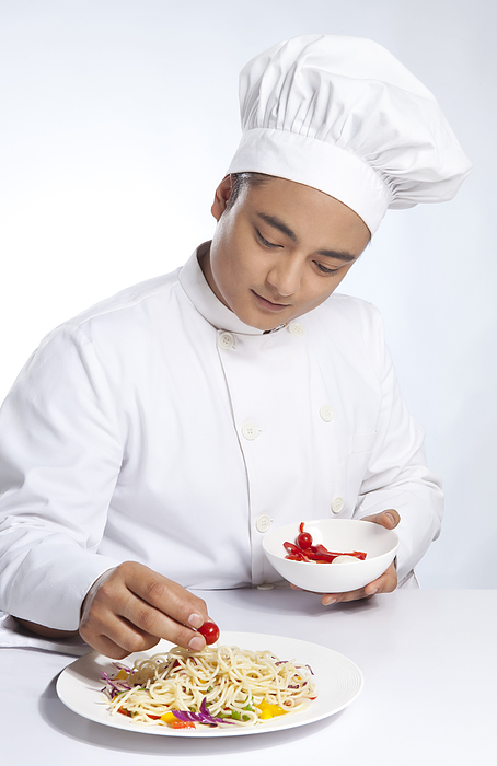 Chef placing cherry tomato on plate of noodles Photograph by Ravi Ranjan