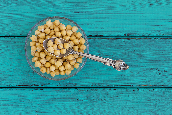 Chick peas on a wood background Photograph by Vlad Fishman