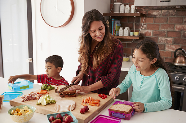 Children Helping Mother To Make School Lunches In Kitchen At Home Photograph by Monkeybusinessimages