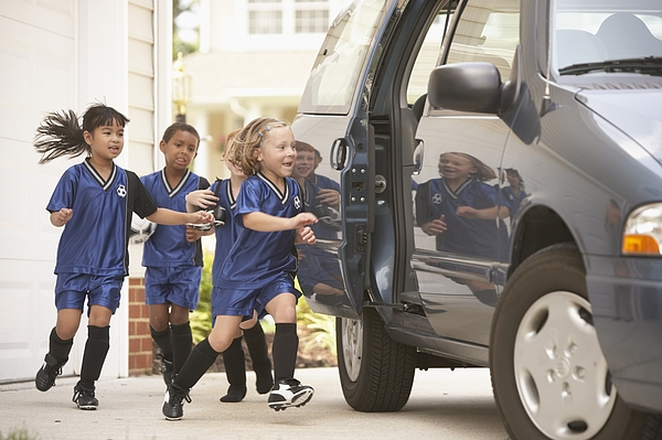 Children in soccer outfits getting into car Photograph by Ariel Skelley