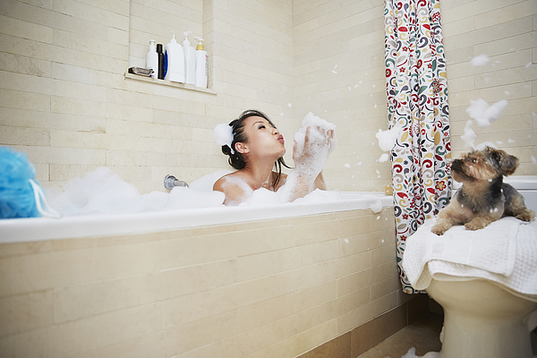 Chinese woman playing in bubble bath with dog Photograph by Jasper Cole