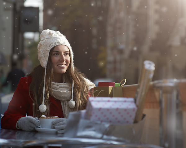 Christmas shopper with coffee and presents in snow Photograph by Dougal Waters