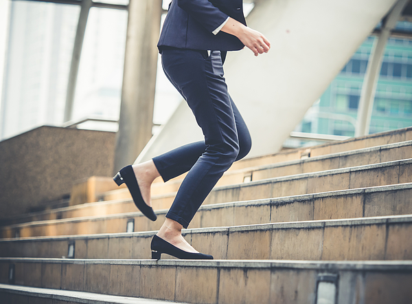 Close up legs of businesswoman walking stepping up stair in modern city, business growth, go up, success, grow up business concept Photograph by Nattakorn Maneerat