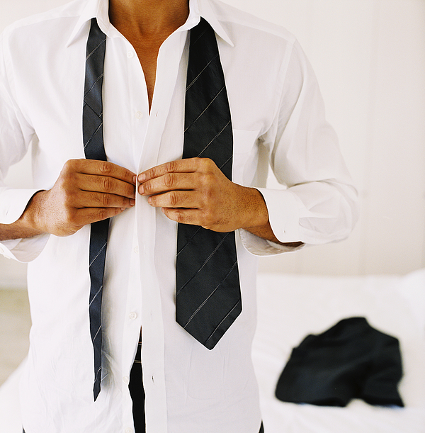 Close-up Of A Mans Hands Buttoning A Shirt Photograph by George Doyle