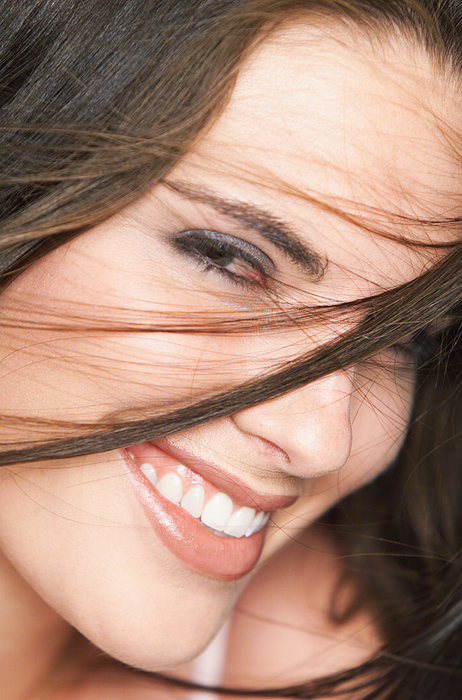 Close Up Of A Young Attractive Caucasian Brunette Who Smile Into The Camera As Her Hair Is Tossed In Front Of Her Face Photograph by Digital Vision
