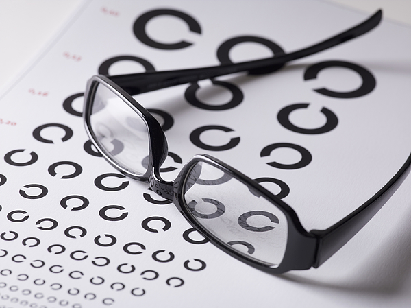 Close-up of glasses on eye exam chart Photograph by Larry Washburn