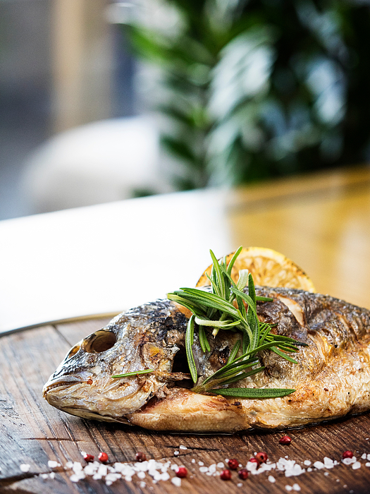 Close-Up Of Grilled Gilthead Bream Garnish With Herbs Served In Plate Photograph by Igor Golovniov / EyeEm