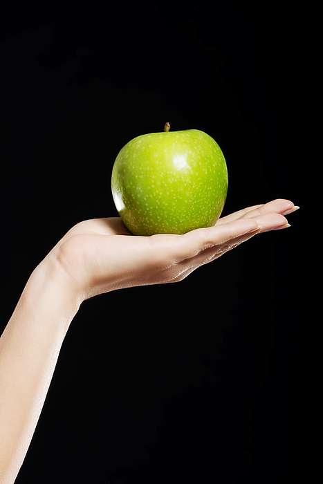 Close-Up Of Hand Holding Apple Against Black Background Photograph by Piotr Marcinski / EyeEm