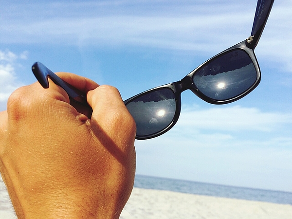 Close-up Of Hand Holding Sunglasses On Beach Against Cloudy Sky Photograph by Sebastian Arning / EyeEm
