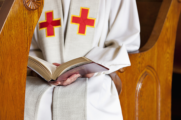 Close up of priest reading Bible Photograph by Robert Nicholas
