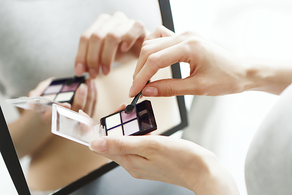 Close up of woman holding eye shadow pallet Photograph by Runstudio