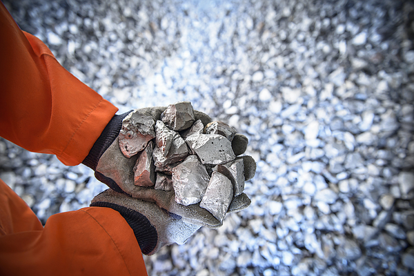 Close up of workers hands holding crushed titanium Photograph by Monty Rakusen