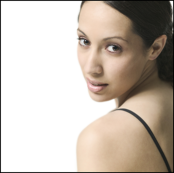 Close Up Shot Of A Brunette Young Adult Woman As She Glances Over Her Shoulder Photograph by Photodisc