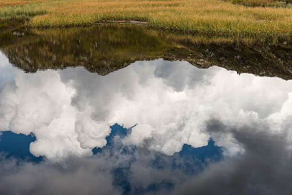 Clouds and mountains reflecting in mountain lake Photograph by Nicolo Sertorio