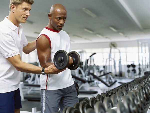 Coach helping a mid adult man exercise with dumbbells Photograph by Stockbyte