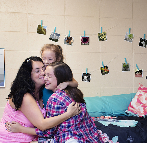College student hugging family in dormitory room Photograph by Hill Street Studios